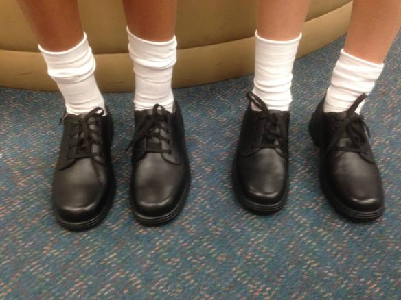 Two girls in boring black laceup school shoes