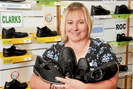Back to school shoe shop lady, holding Harrison t-bars, Clarks and Roc shoes